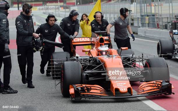 McLaren Honda's Belgium driver Stoffel Vandoorme is pushed by his mechanics after a break down at the Circuit de Catalunya on February 28 2017 in...