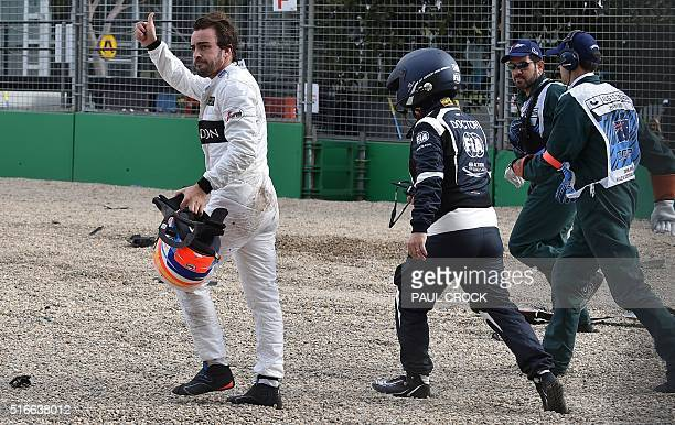 McLaren Honda's Spanish driver Fernando Alonso gives the crowd the thumbs-up after crashing with Haas F1 Team's Brazilian driver Esteban Gutierrez...