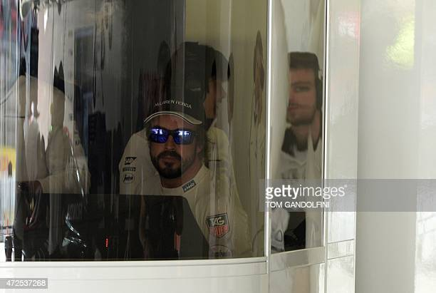 McLaren Honda's Spanish driver Fernando Alonso sits behind a screen in the pits during the first practice session at the Circuit de Catalunya on May...