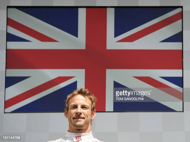 McLaren Mercedes' British driver Jenson Button miles on the podium at the Spa-Francorchamps circuit on September 2, 2012 in Spa after winning the...