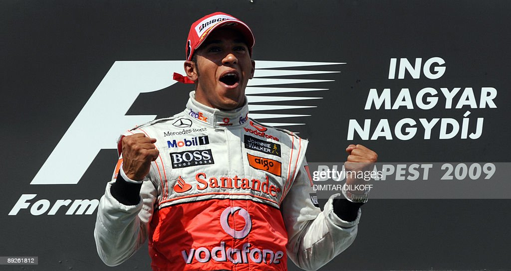 McLaren Mercedes' British driver Lewis Hamilton celebrates on the podium of the Hungaroring racetrack on July 25, 2009 in Budapest, after the Hungarian Formula One Grand Prix. McLaren Mercedes' British driver Lewis Hamilton won the race ahead of Ferrari's Finnish driver Kimi Raikkonen and Red Bull's Australian driver Mark Webber.