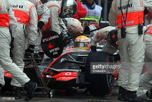 McLaren Mercedes mechanics serve for Lewis Hamilton of Great Britain during his pitstop on his way to winning the Japanese Formula One Grand Prix at...