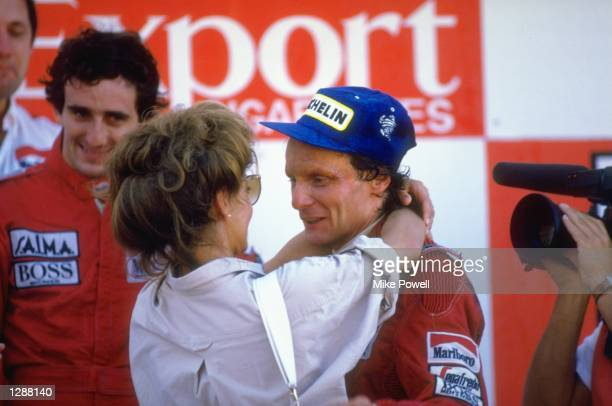 McLaren TAG driver Niki Lauda of Austria is congratulated by his wife watched by team mate Alain Prost after the Portuguese Grand Prix at the Estoril...