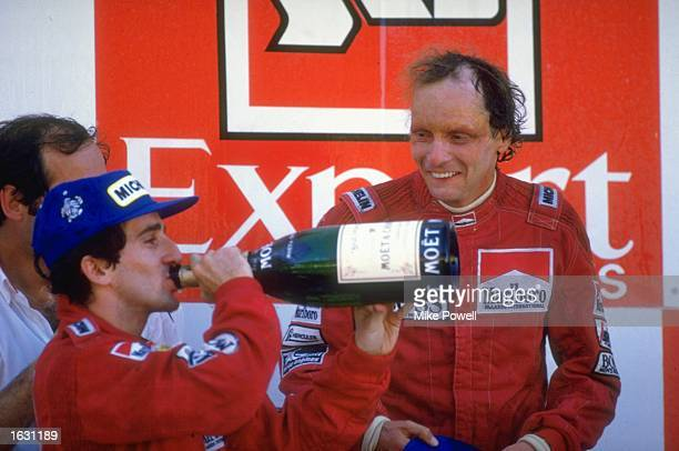 McLaren TAG drivers Alain Prost of France and Niki Lauda of Austria celebrate after the Portuguese Grand Prix at the Estoril circuit in Portugal....