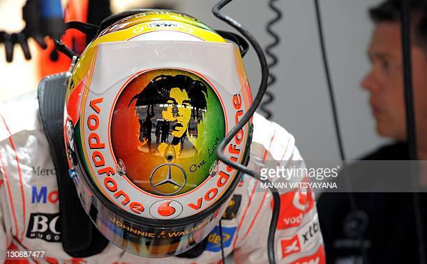 McLarenMercedes driver Lewis Hamilton of Britain gets into his car wearing a helmet adorned with a portrait of late Jamaican reggae musician Bob...