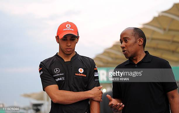 McLarenMercedes driver Lewis Hamilton of Britain listens to his father Anthony Hamilton while walking on the pit lane after the qualifying session...