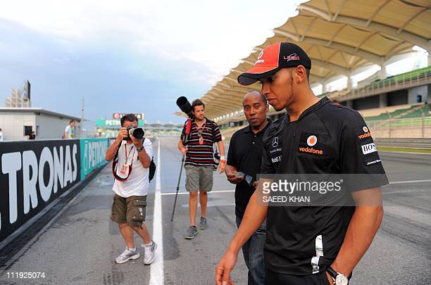 McLarenMercedes driver Lewis Hamilton of Britain talks to his father Anthony Hamilton while walking on the circuit after the qualifying session for...