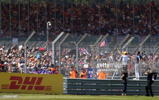 McLaren's British driver Lando Norris and Williams' British driver George Russell wave to the crowd ahead of the Formula One British Grand Prix motor...