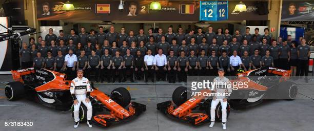 McLaren's Spanish driver Fernando Alonso and Belgian driver Stoffel Vandoorne pose with the McLaren team in the pits before the start of the...