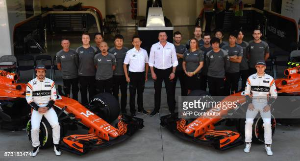 McLaren's Spanish driver Fernando Alonso and Belgian driver Stoffel Vandoorne pose with part of the McLaren team in the pits before the start of the...