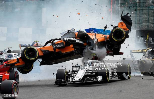 McLaren's Spanish driver Fernando Alonso crashes ontop of Sauber F1's Monegasque driver Charles Leclerc during the first lap of the Belgian Formula...