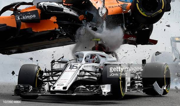 TOPSHOT McLaren's Spanish driver Fernando Alonso crashes ontop of Sauber F1's Monegasque driver Charles Leclerc during the first lap of the Belgian...