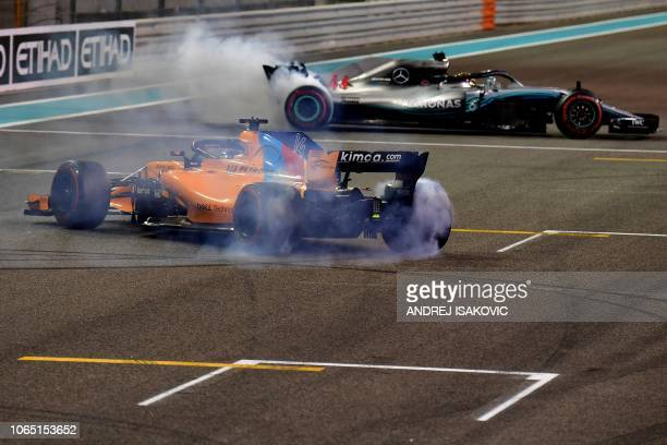 TOPSHOT McLaren's Spanish driver Fernando Alonso drifts with his car after his last F1 race next to Mercedes' British driver Lewis Hamilton at the...