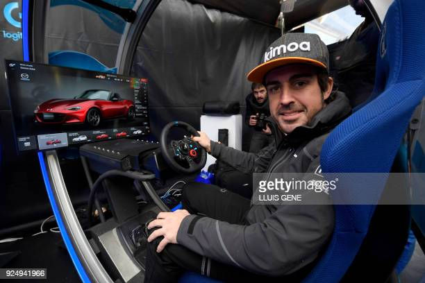 McLaren's Spanish driver Fernando Alonso sits at the Logitech virtual reality simulator at the Mobile World Congress the world's biggest mobile fair...