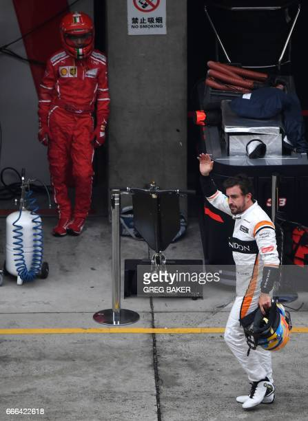 McLaren's Spanish driver Fernando Alonso walks through the pit lane after retiring from the Formula One Chinese Grand Prix in Shanghai on April 9...