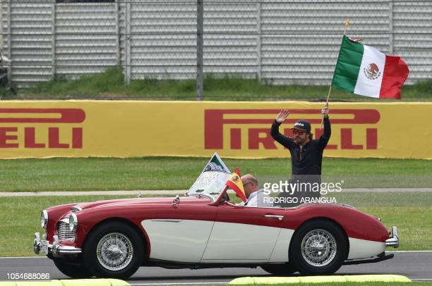 McLaren's Spanish driver Fernando Alonso , waves a Mexican national flag from a classic car, during the drivers' parade, prior to the start of the F1...