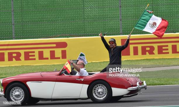 McLaren's Spanish driver Fernando Alonso, waves to the fans from a classic car during the drivers' parade, prior to the start of the F1 Mexico Grand...