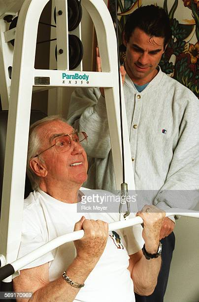 LSMcMahon10224RM8 Ed McMahon works out at home with the help of trainer Jon Jon Park McMahon is using a weight machine McMahoon and his wife Pam are...