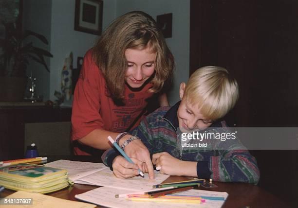 Mädchen hilft ihrem Bruder bei den Schulaufgaben 1995