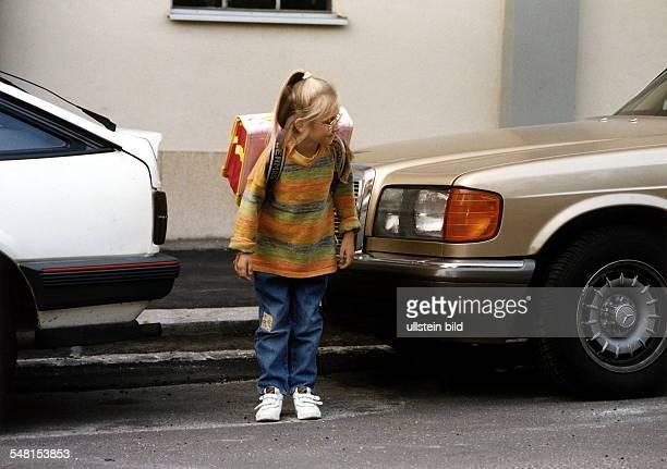 Mädchen mit Schulmappe steht am Strassenrand zwischen zwei Autos und sieht nach links, um die Strasse zu überqueren - 1997
