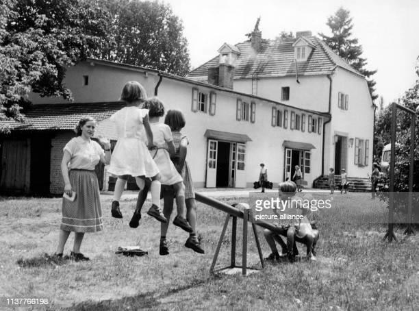 Mädchen probieren am die Wippe vor dem Ferienheim in Görsdorf in Brandenburg aus Am Tag zuvor hatte die Werksleitung des Berliner Großbetriebes VEB...