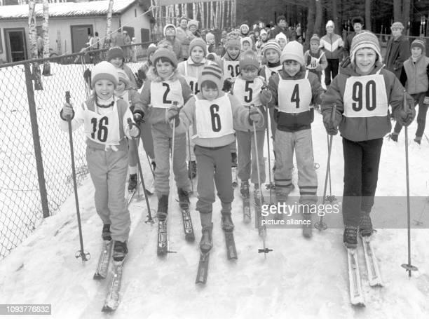 Mädchen und Jungen sind im Januar 1986 gut gelaunt auf dem Weg zum Start der LanglaufWettbewerbe bei der Kinder und Jugendspartakiade in den...