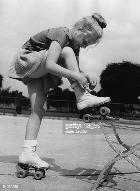 Mädchen vom Berliner Rollschuhclub schnürt sich die Rollschuhe zu 1952