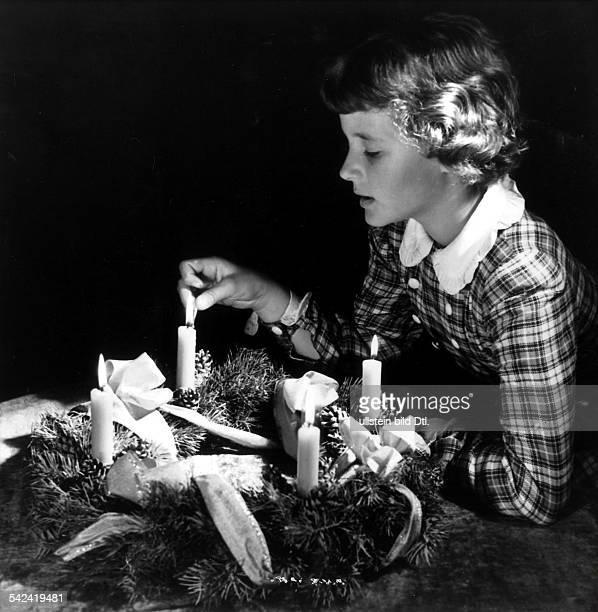 Mädchen zündet Kerze eines Adventskranzes an 1950
