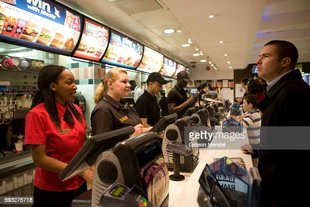 MdDonald's workers dressed in their new more stylish uniforms take orders from customers at the new trendy coffee bar style ambience and design at...
