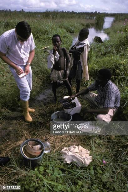 Médecins français coopérant avec des étudiants béninois faisant des relevés d'eau dans un marais pour étudier les parasites en décembre 1988 au Bénin
