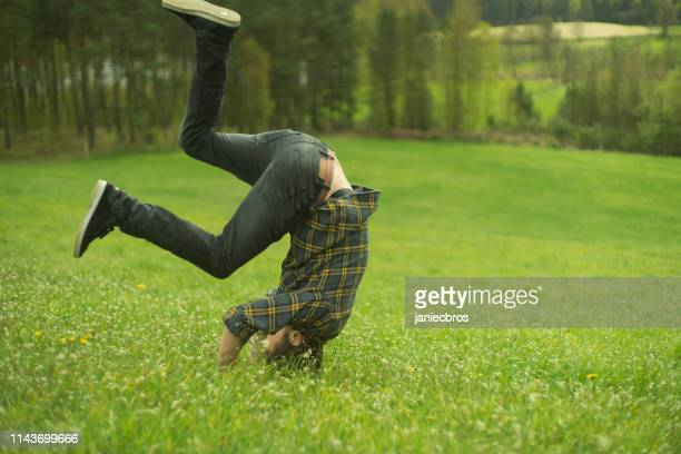 meadow acrobatics. man fooling around - somersault stock pictures, royalty-free photos & images