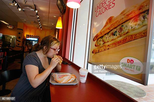Meaghan Cooligan eats a Veggie Egg White Flatbread sandwich at a Dunkin' Donuts restaurant August 6, 2008 in Miami, Florida. The sandwich is one of...