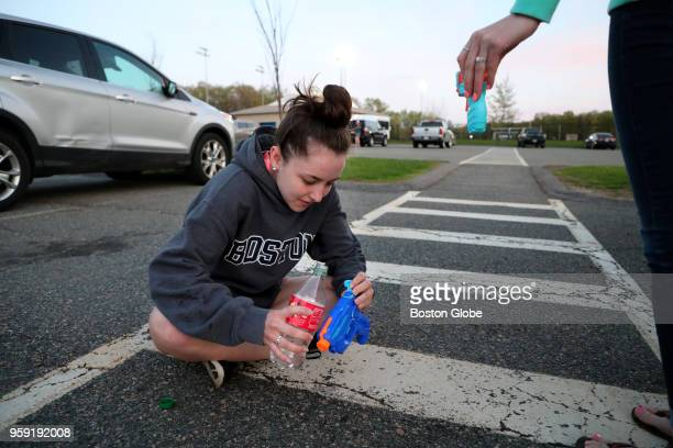 Meaghan Downing a senior at Medway High School loads her squirt gun in the school's parking lot as she gets ready to participate in the 'Senior Soak'...