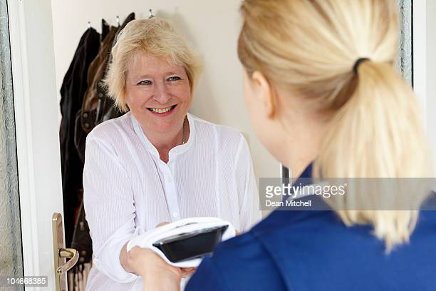 meal being delivered to senior woman at home - dean foods stock photos and pictures