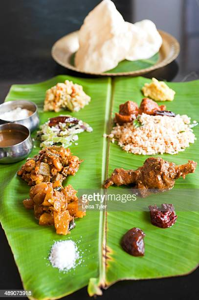 A meal consisting of chicken and fish curry different vegetable dishes plus a handful of chutneys dal yoghurt rice and papadams served on a banana...