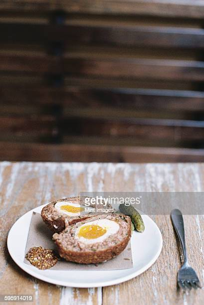 A meal on a plate, a scotch egg cut in half with garnishes.
