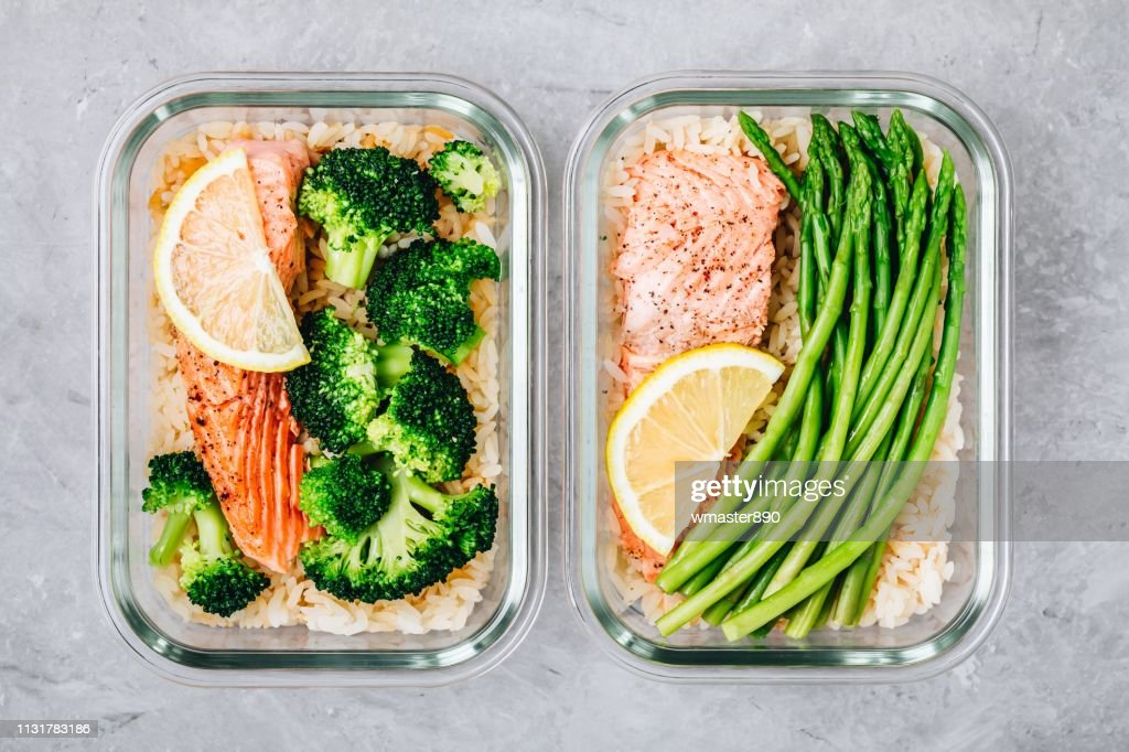 Meal prep lunch box containers with baked salmon fish, rice, green broccoli and asparagus : Stock Photo
