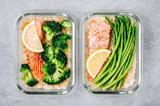 Meal prep lunch box containers with baked salmon fish, rice, green broccoli and asparagus 1131783186