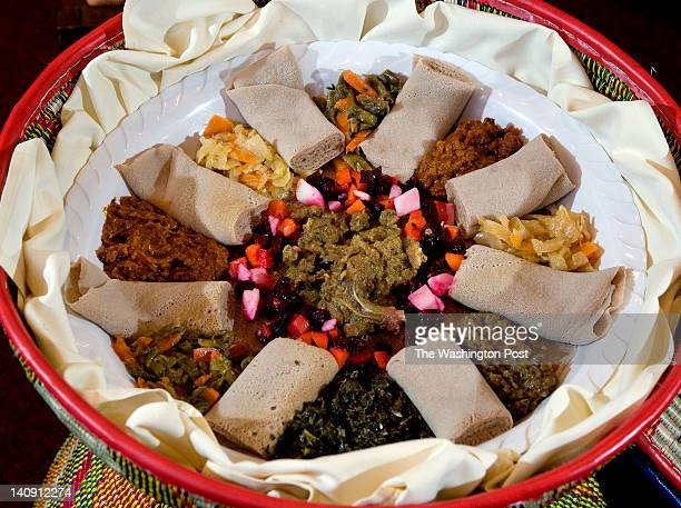 A meal served in a colorful Ethiopian basket table at Sheba Ethiopian Restaurant in Fairfax VA on February 29 2012 At center is Beg Alitcha with...