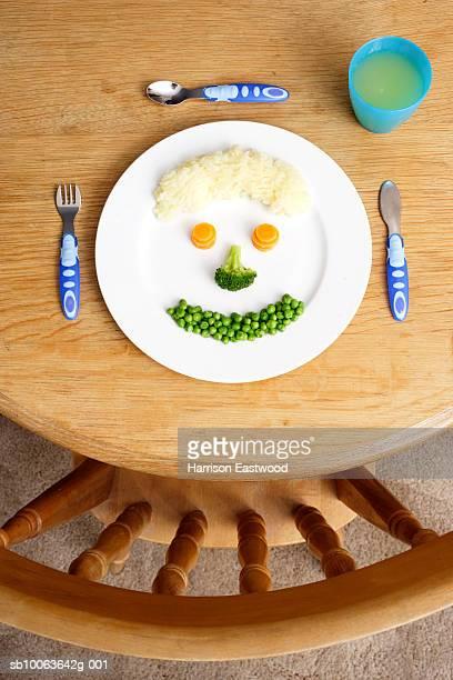 Meal with smiley face on plate on table, overhead view