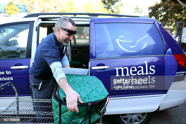 Meals On Wheels of San Francisco driver Jim Fleming loads meals into a van before making deliveries on February 27 2013 in San Francisco California...