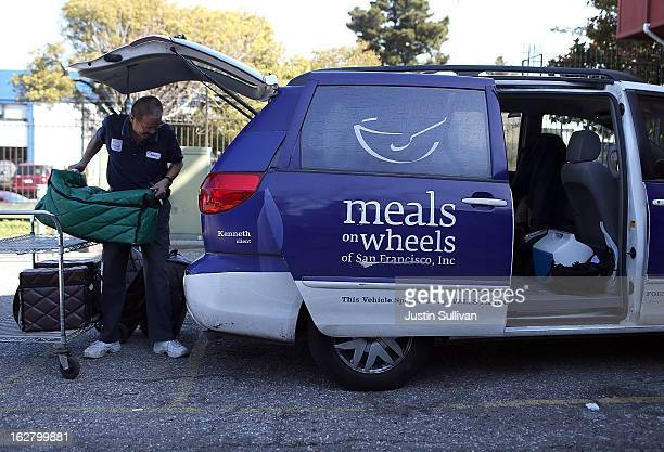 Meals On Wheels of San Francisco driver loads meals into a van before making deliveries on February 27 2013 in San Francisco California Programs for...