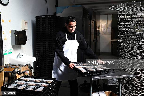 Meals On Wheels of San Francisco worker stacks trays of prepared meals on February 27 2013 in San Francisco California Programs for the poor like...