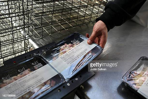 Meals On Wheels of San Francisco worker takes prepared meals off of a conveyor belt on February 27 2013 in San Francisco California Programs for the...