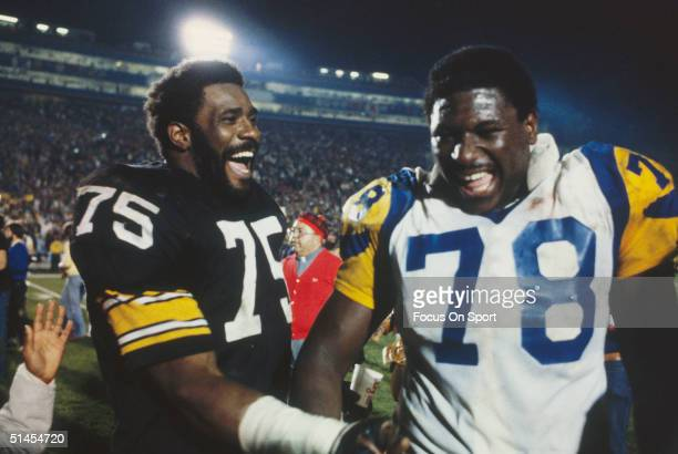 Mean Joe Greene of the Pittsburgh Steelers and Jackie Slater of the Los Angeles Rams joke around on the field after Super Bowl XIV at the Rose Bowl...