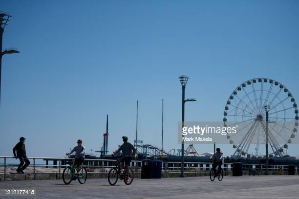 A mean wearing a mask sits on the boardwalk railing as cyclists pedal past during the coronavirus pandemic on May 7 2020 in Atlantic City New Jersey...