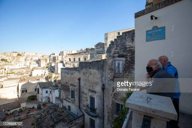 Mean wearing masks look out from Belvedere Luigi Guerricchio on May 23 2020 in Matera Italy Restaurants bars cafes hairdressers and other shops have...