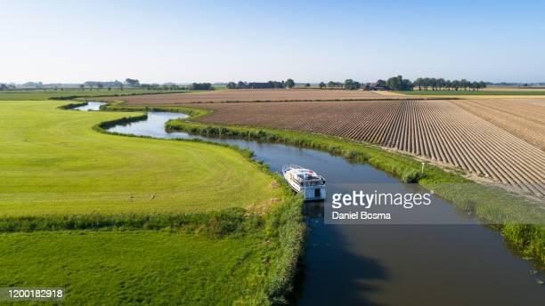 meandering river with boat in the middle of an agricultural landscape - groningen provincie stockfoto's en -beelden