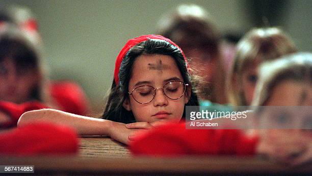 MEashpray0212AS––TUSTIN––St Cecilia 2nd grader Aine Sandfort prays after receiving ashes on her forehead during Ash Wednesday children's mass at St...