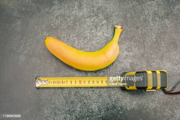 measure tape and banana.size matters - meter unit of length stock pictures, royalty-free photos & images